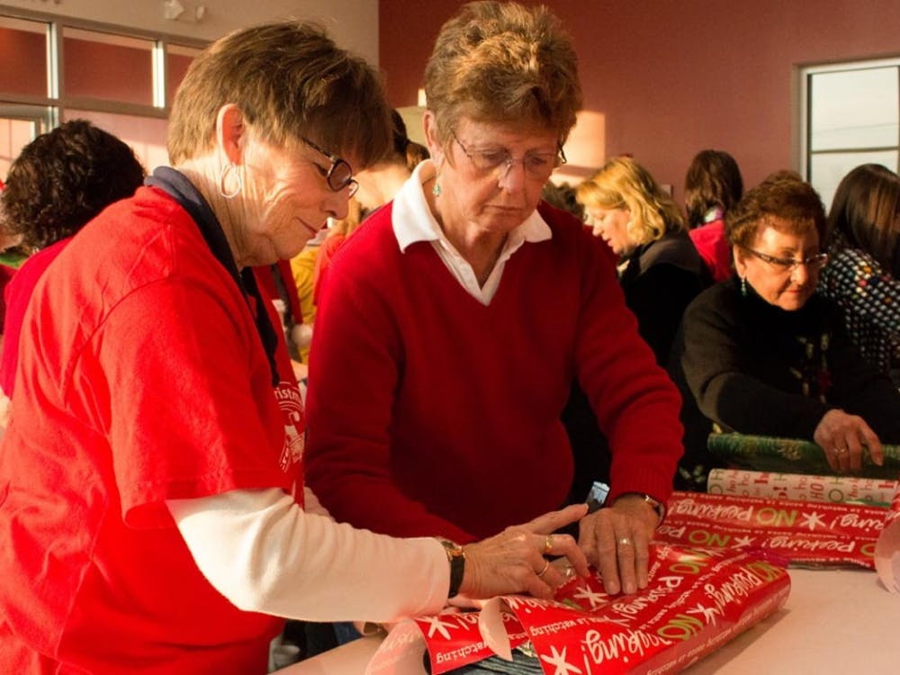 Marsha Kibby, right, and Norma Hiestand, left, wrap gifts for the Secret Families Christmas Charity on Saturday. Volunteers bought gifts at 6 a.m. at Meijer and then wrapped the gifts at Toyota of Muncie. DN PHOTO TAYLOR IRBY
