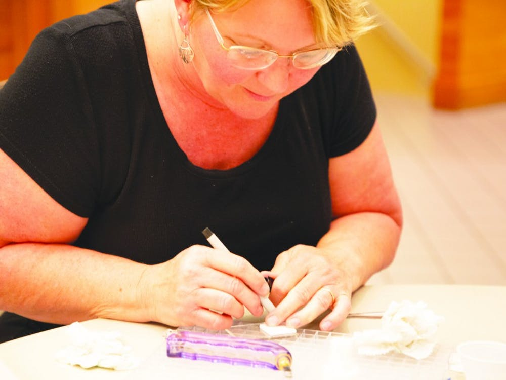 Jackie Davis marks a glass square she is working with to create one of several pieces at a Minnistrista glass workshop Sept. 12, 2019. Alyssa Cooper, DN