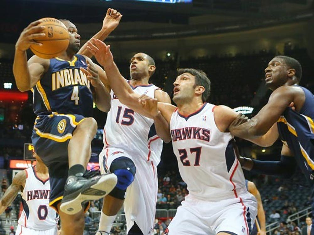 The Atlanta Hawks' Al Horford and Zaza Pachulia force the Indiana Pacers' Sam Young to pass it off under the basket during first-half action at Philips Arena in Atlanta on Nov. 7, 2012. The Pacers took on the Heat on Tuesday night, winning 87-77.  MCT PHOTO