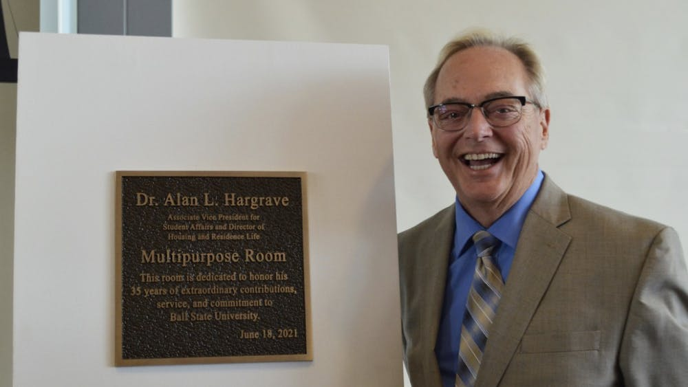 Alan L. Hargrave poses with the new Multipurpose Room sign on Friday, June 18, 2021.