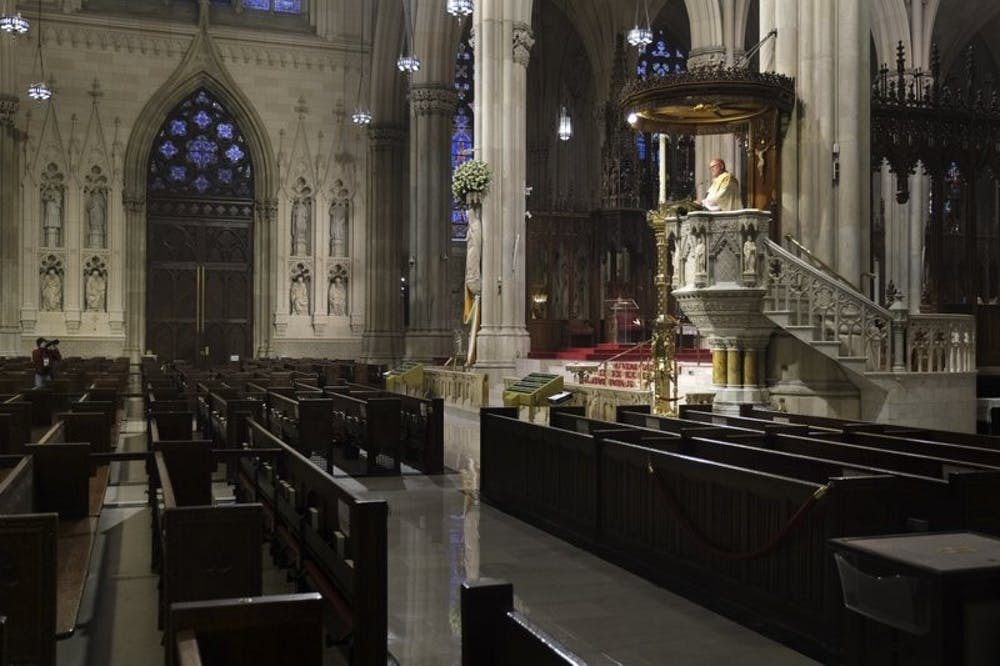 <p>Archbishop Timothy Dolan, right, delivers his homily over empty pews as he leads an Easter Mass at St. Patrick's Cathedral in New York, Sunday, April 12, 2020. Due to coronavirus concerns, no congregants were allowed to attend the Mass but it was broadcast live on a local TV station. <strong>AP Photo/Seth Wenig</strong></p>