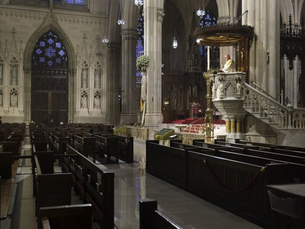 Archbishop Timothy Dolan, right, delivers his homily over empty pews as he leads an Easter Mass at St. Patrick's Cathedral in New York, Sunday, April 12, 2020. Due to coronavirus concerns, no congregants were allowed to attend the Mass but it was broadcast live on a local TV station. AP Photo/Seth Wenig