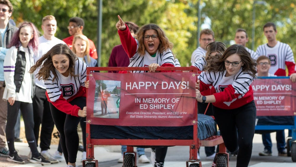 Students from the Ball State University Singers organization take off during the 2019 Ball State University Bed Race Oct. 18, on Riverside Ave. Bed races have been a Homecoming Week traditional at BSU since 1980. Kyle Crawford, Byte File