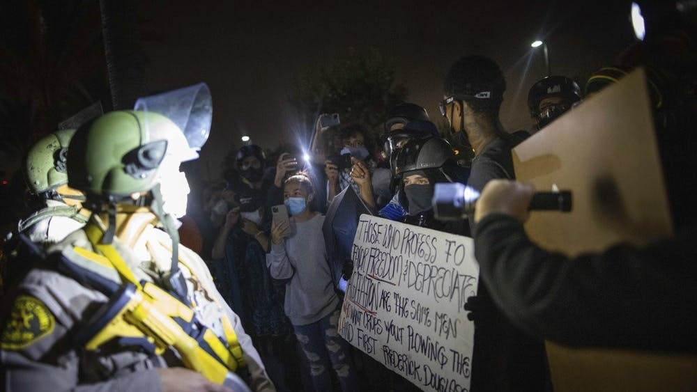 Protesters clash with deputies of the Los Angeles Sheriff's Department during protests following the death of Dijon Kizzee on Monday, Aug. 31, 2020, in Los Angeles, Calif. (AP Photo/Christian Monterrosa)