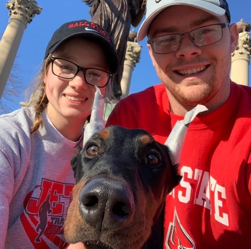 Sophomore Molly Ellenberger and her fiance, Tyler LaFontaine, pose with their dog, Moose, in front of Beneficence. The two got Moose from a breeder in November 2019. Molly Ellenberger, Photo Provided.