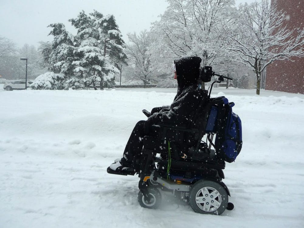 Colin McIntire, a junior computer science major, passes Bracken Library in the snow. McIntire said he had trouble crossing McKinley Avenue, but doesn