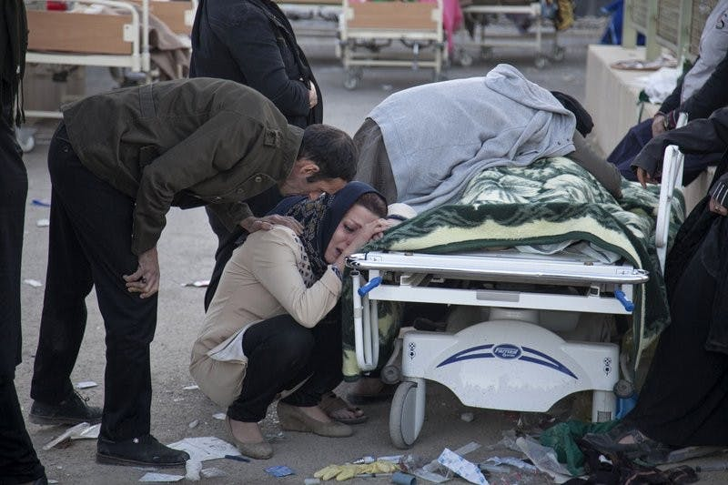 In this photo provided by Tasnim News Agency, relatives weep over the body of an earthquake victim, Sarpol-e-Zahab western Iran, Monday, Nov. 13, 2017. Authorities reported that a 7.3 magnitude earthquake struck the Iraq-Iran border region on Monday and killed more than 300 people in both countries, sent people fleeing their homes into the night and was felt as far west as the Mediterranean cost. Farzad Menati, Tasnim News Agency via AP