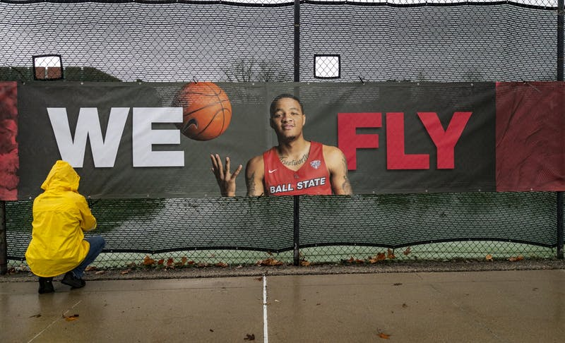 "A person ties a ""We Fly"" marketing banner on Ball State's campus. The university's new ""We Fly"" marketing campaign includes new banners, signage, billboards, digital advertisements and a commercial. Ball State University, Photo Provided"