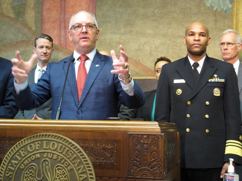 Louisiana Gov. John Bel Edwards speaks about the new coronavirus while U.S. Surgeon General Jerome Adams, right, listens on Thursday, March 12, 2020, in Baton Rouge, La. The number of cases of the COVID-19 disease caused by the virus are on the rise in Louisiana. (AP Photo/Melinda Deslatte)