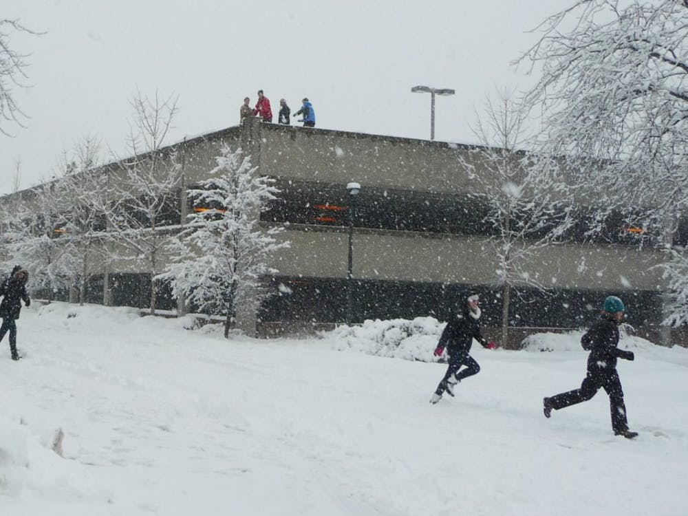Students atop a parking garage ambush unsuspecting walkers with snowballs. The group said many of their victims played along with the prank. DN PHOTO SAM HOYT