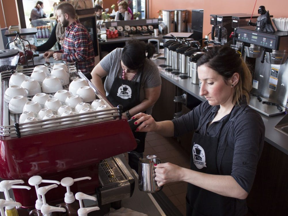 Employees of The Caffeinery serve customers in 2014. The coffee shop roasts its own beans and serves specialty lattes. Ross May, DN