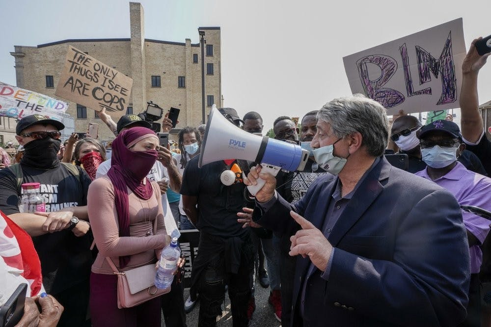 <p>Kenosha Mayor John Antaramian, right, speaks to protesters using a megaphone, Monday, Aug. 24, 2020, in Kenosha, Wis. Kenosha police shot a man Sunday evening, setting off unrest in the city after a video appeared to show the officer firing several shots at close range into the man&#x27;s back. <strong>(AP Photo/Morry Gash)</strong></p>