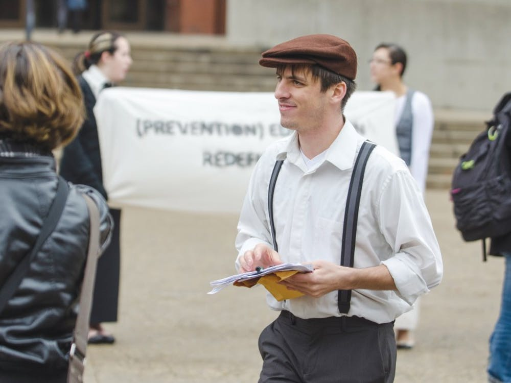 Matthew Smith, co-director of Amnesty International, hands out fliers to people encouraging them to sign a petition to advise the university to expand the sexual assault programs Dec. 4 outside of Bracken Library. Protestors adapted speeches and outfits from the 1920s to tie in the women