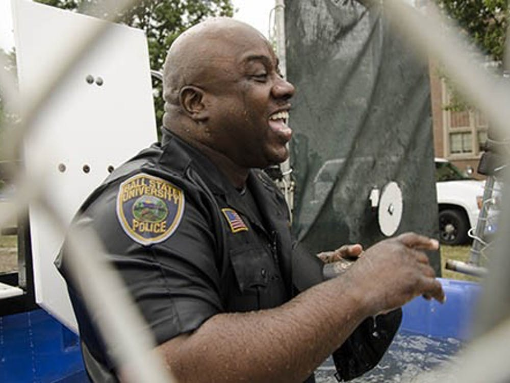 Officer Terrell Smith of the University Police Department laughs Friday afternoon after being dunked by bystanders during UPD