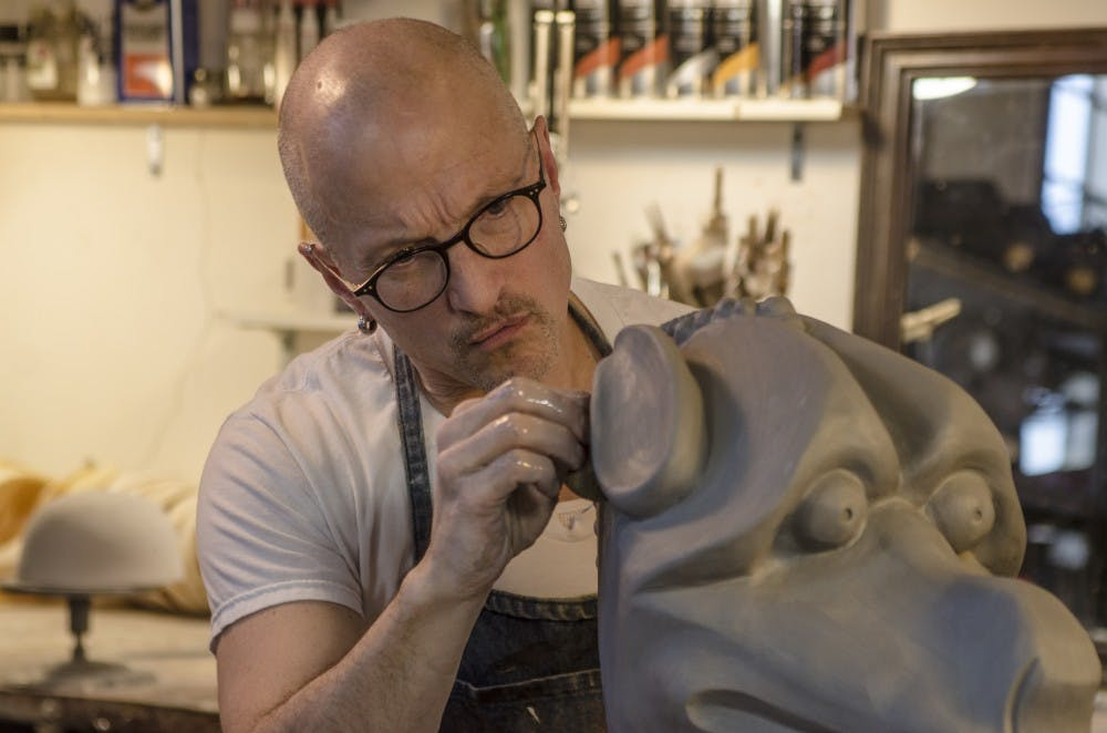 <p>Jonathan Becker carves a clay mold at his studio in Muncie March 25 that will eventually be cast and become a mask. <strong>J.A. Fields, DN</strong></p>