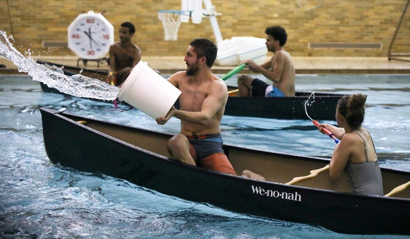 Freshman Peter Sherfey throws water across the pool while freshman Lexi Leisure uses a super soaker to squirt water into another team's canoe Feb. 5, 2020, at Ball Gymnasium pool. Their team, Exes and Flexes, won the event. Hannah Gunnell, DN
