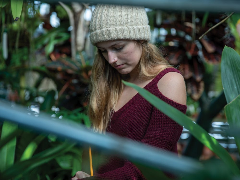 Sam Luginbuhl, senior wildlife biology major, takes notes on the growth of different plants Feb. 14, 2020, at Dr. Joe and Alice Rinard Orchid greenhouse. A part of Luginbuhl's job is to measure the growth rate of the plants in the greenhouse. Jacob Musselman, DN
