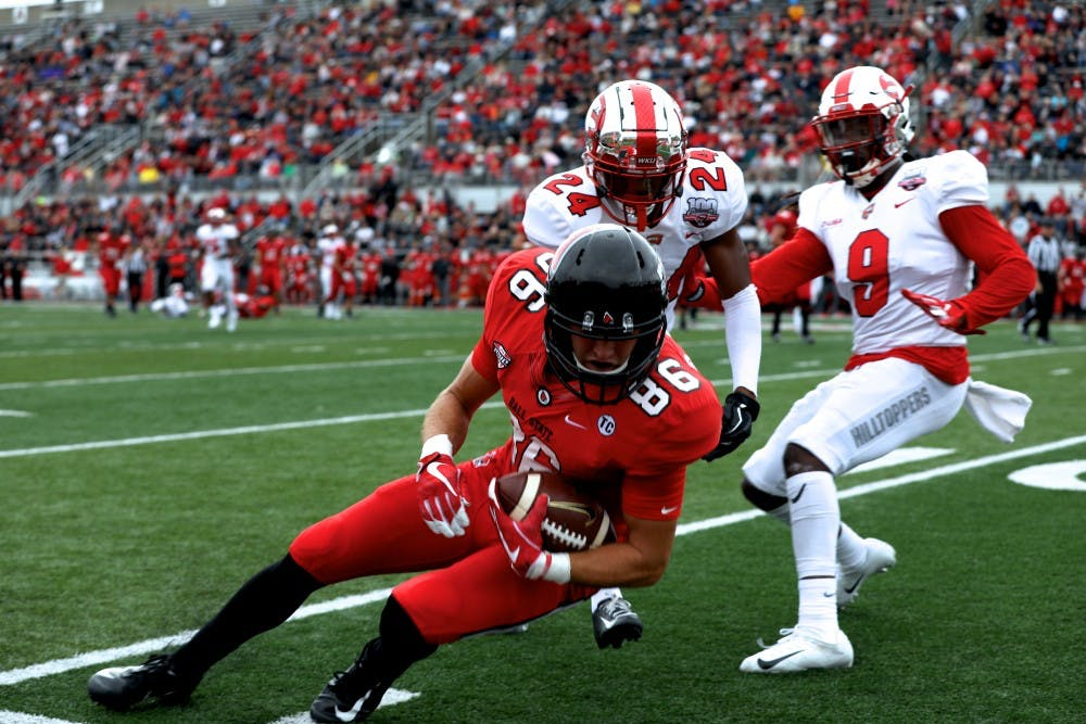<p>Redshirt junior Riley Miller braces the ball for a tackle from a Western Kentucky player Sept. 22, 2018, at Scheumann Stadium. The Cardinals lost to the Hilltoppers 28-20. Rebecca Slezak,DN</p>