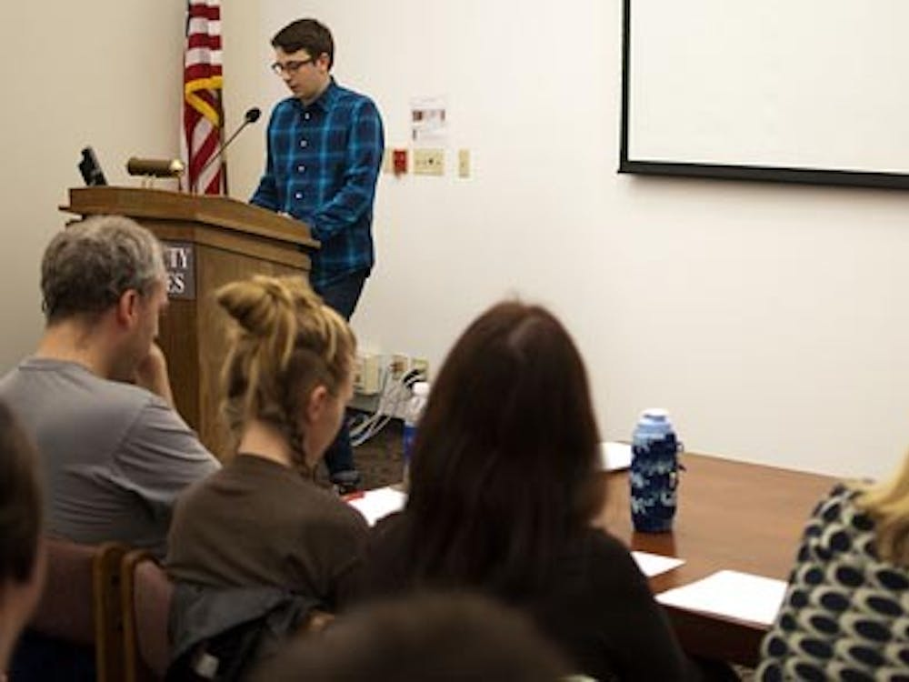 Austin Hayden reads a story, while judges look on during the Literary Death Match on Monday in Bracken Library. The readers were judged during the event and had already passed through two judging heats prior to the event. DN PHOTO BOBBY ELLIS