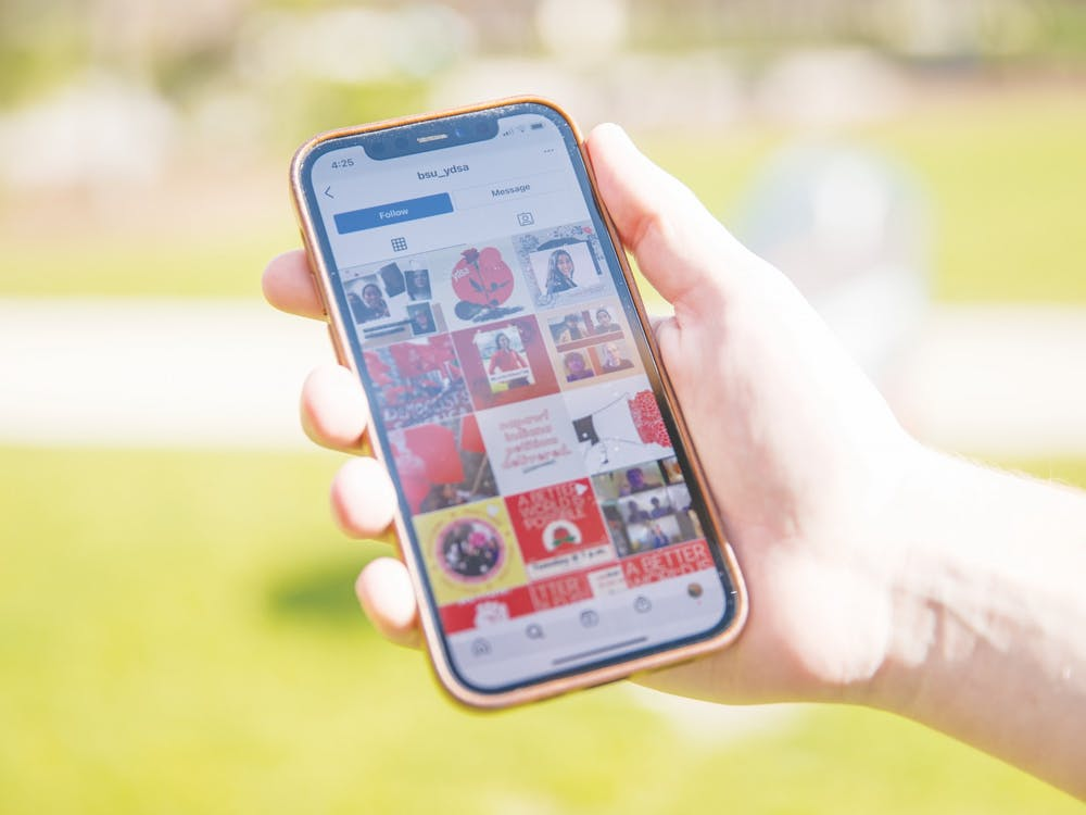 The Ball State Young Democratic Socialists of America's Instagram page is pulled up on a phone March 31, 2021, outside of the Atrium. The new political organization has used social media for outreach early in its development. Jaden Whiteman, DN Illustration