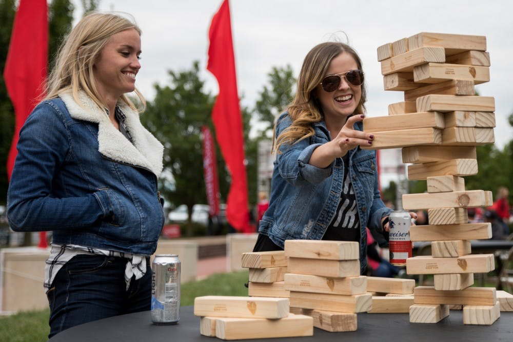 <p>Kristen Olson and Taylor West play Jenga in Charlie Town Sept. 22, 2018, before Ball State played Western Kentucky in football. Charlie Town is a tailgating opportunity, and takes place before every home football game. <strong>Eric Pritchett, DN File</strong></p>