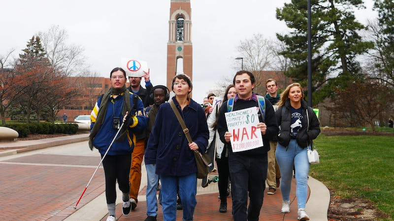 Ball State students hold signs and march Jan. 13, 2020, down McKinley Avenue for an anti-war protest. The protest was held by Ball State Democrats. Jake Helmen, DN