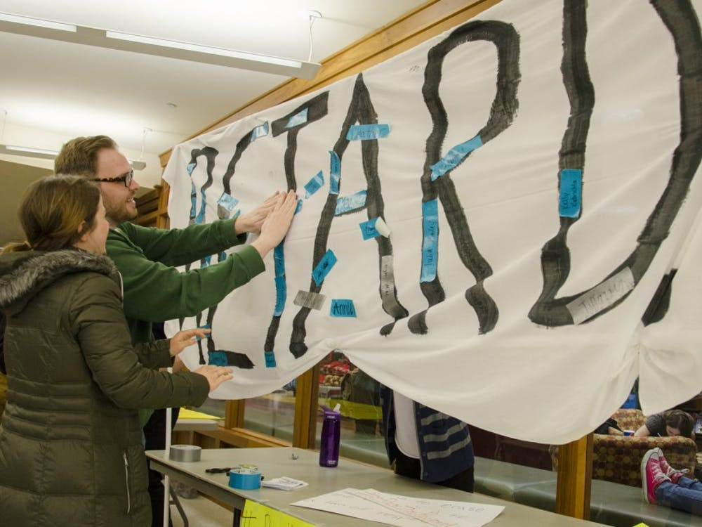 Alumnus Andy Roets and junior art education major Taylor West place a piece of tape with their name on in to support the end of the R word. DN PHOTO BREANNA DAUGHERTY