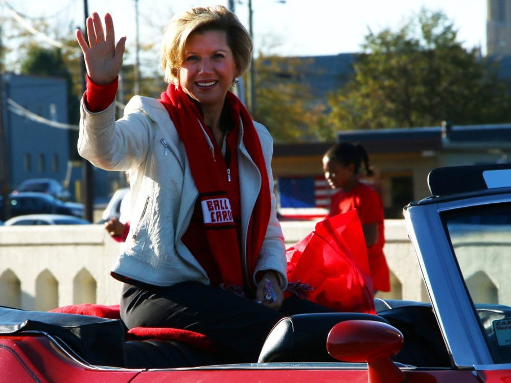 Ball State President Jo Ann Gora waves to the crowd at the Homecoming Parade on the morning of Oct. 12. Muncie Mayor Dennis Tyler also was in the parade. DN PHOTO TAYLOR IRBY