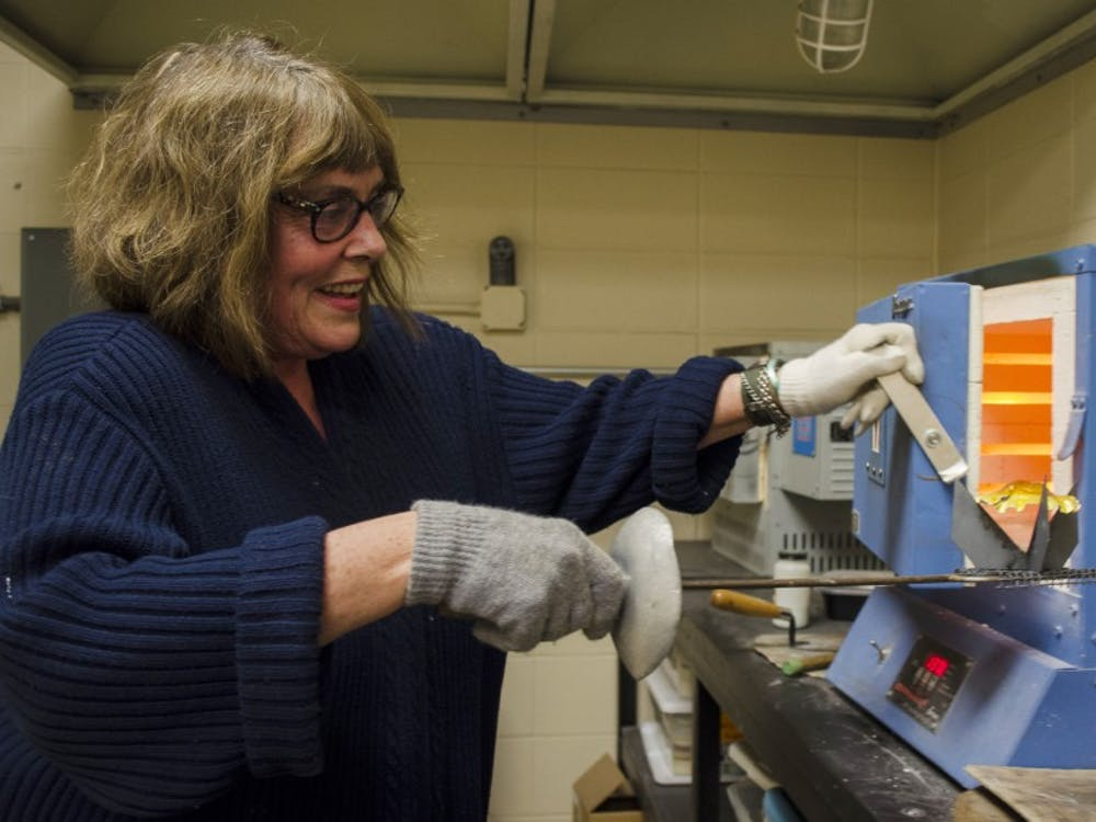 Patricia Nelson creates a piece of vitreous enamel on Oct. 16. Vitreous enamel is made from powdered glass. DN PHOTO BREANNA DAUGHERTY