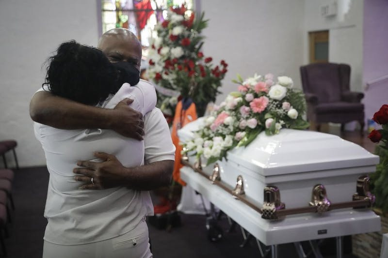 FILE - In this July 21, 2020, file photo, Darryl Hutchinson, facing camera, is hugged by a relative during a funeral service for Lydia Nunez, who was Hutchinson's cousin at the Metropolitan Baptist Church in Los Angeles. Nunez died from COVID-19. (AP Photo/Marcio Jose Sanchez, File)