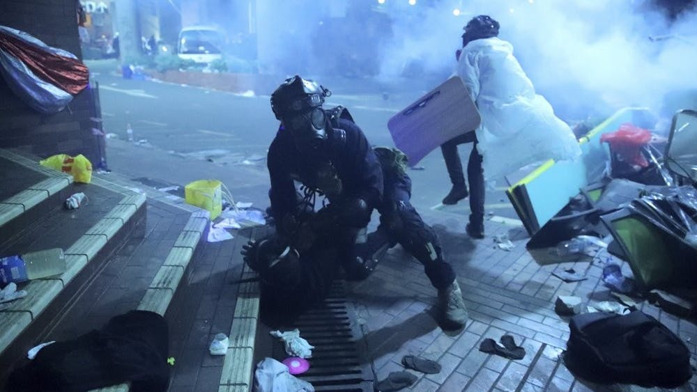 A policeman in riot gear detains a protester outside of Hong Kong Polytechnic University as police storm the campus in Hong Kong, early Monday, Nov. 18, 2019. Fiery explosions were seen early Monday as Hong Kong police stormed into a university held by protesters after an all-night standoff. (AP Photo/Kin Cheung)