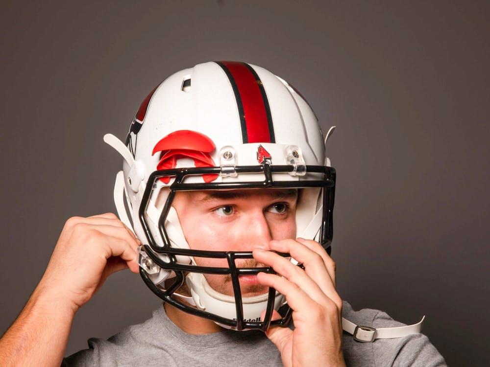 Redshirt freshman Mitchell Carter puts on his helmet Nov. 25, 2019. Jacob Musselman, DN Illustration