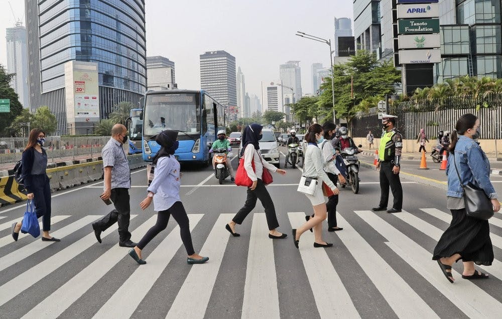 People, wearing a face mask as a precaution against the new coronavirus outbreak, walk on a pedestrian crossing at the main business district in Jakarta, Indonesia, Monday, Sept. 14, 2020. Indonesia's capital on Monday begins to reimpose large-scale social restrictions to control a rapid expansion in the virus cases. (AP Photo/Tatan Syuflana)