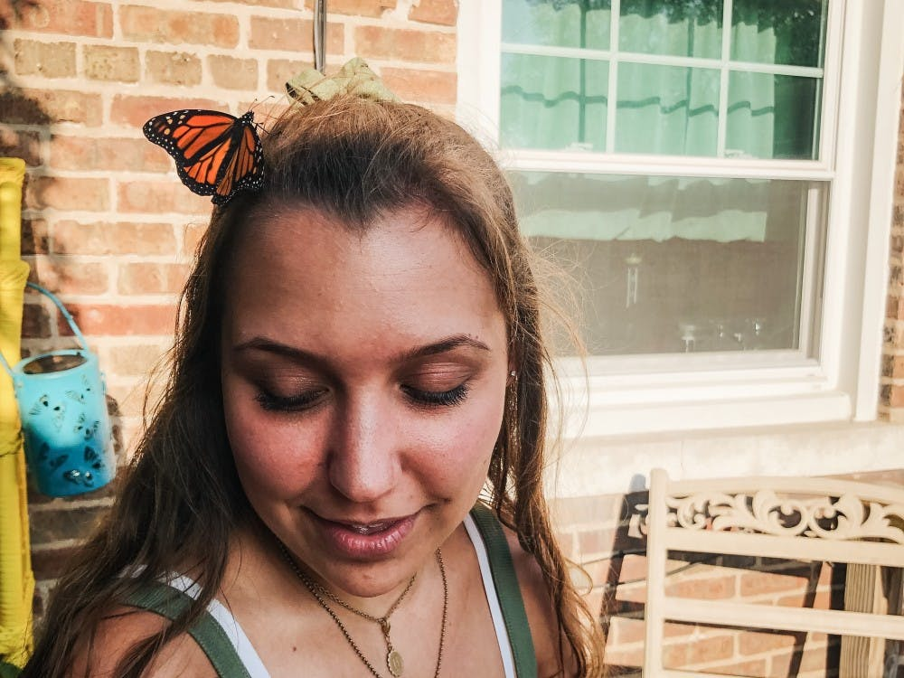 Taylor Smith helps her aunt release butterflies in her backyard. Smith's aunt released a butterfly onto Smith's hair where it sat like a hairpin for a moment before flying away. Taylor Smith, Photo Provided