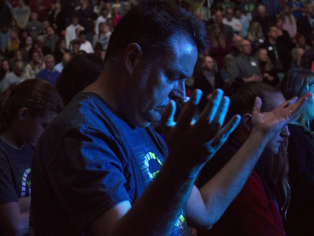 A man bows his head and raises his hands up in the air during a moment of prayer at the Fileds of Faith Nov. 1, 2018, at Worthen Arena. The event began at 6:30 p.m. Patrick Murphy, DN