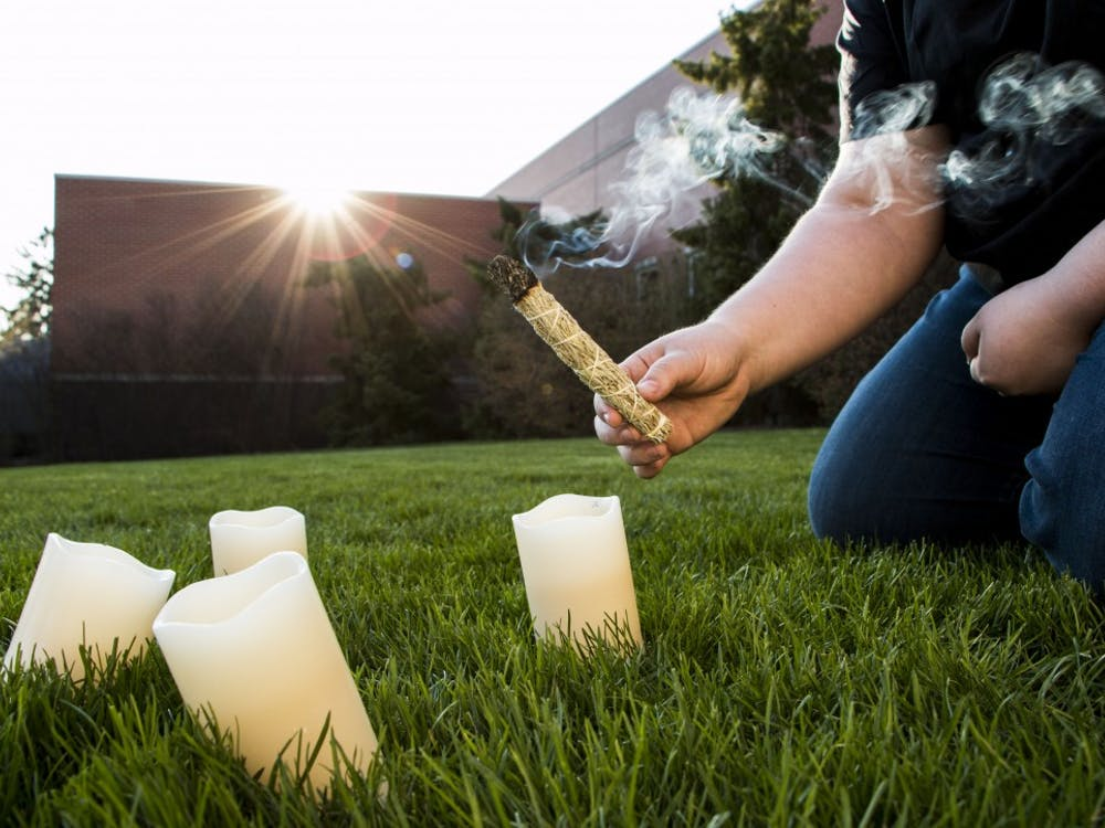 A student sets up a North American Wiccan spring sage blessing. The ritual is a celebration bringing in the new season after winter. DN PHOTO TAYLOR IRBY