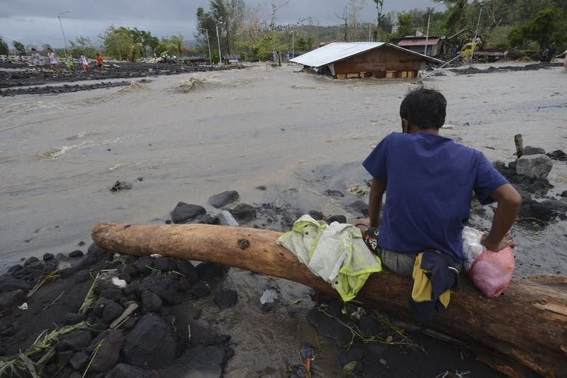 A man looks as floodwaters inundate an area as Typhoon Goni hit Daraga, Albay province, central Philippines, Sunday, Nov. 1, 2020. The super typhoon slammed into the eastern Philippines with ferocious winds early Sunday and about a million people have been evacuated in its projected path, including in the capital where the main international airport was ordered closed. (AP Photo)