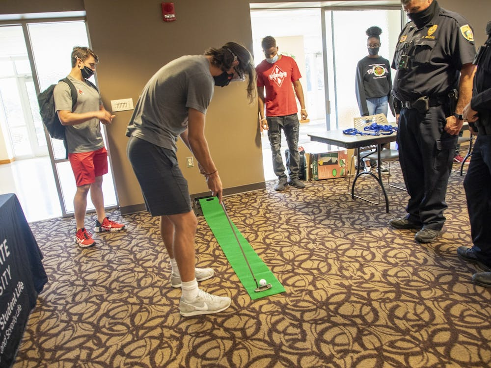 """Freshman chemical engineering major Issac Daniels plays mini golf with """"drunk goggles"""" on, while onlookers watch in the L.A. Pittenger Student Center Oct. 20, 2021. The mini golf was stationed at the campus police table at the """"Save Your Beers For Another Day"""" event. Hannah Amos, DN"""