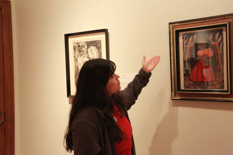 "Jasmine Romero, museum docent, explains the details of artist Diego Rivera's ""Niña con flores"" Feb. 23, 2020. Romero pointed out the candles and flowers in the watercolor painting as inspired by the traditionally Hispanic day of remembrance Día de los Muertos. Brooke Kemp, DN"