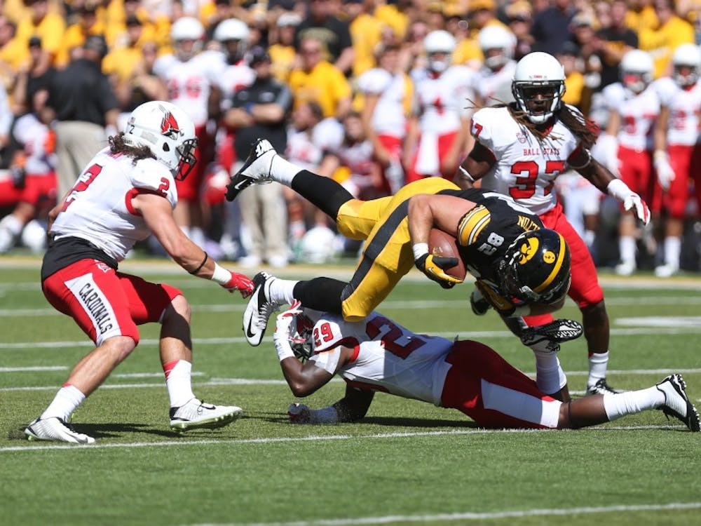 Iowa tight end Ray Hamilton gets tackled by Ball State strong safety Brian Jones on Sept. 6 in Kinnick Stadium. Iowa defeated Ball State, 17-13. (The Daily Iowan/Tessa Hursh)