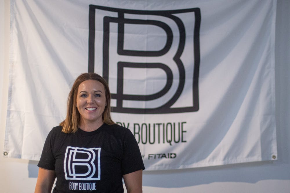 <p>Brittney  Russell poses in front of a Body Boutique flag Sept. 10, 2020, at Body Boutique. Russell started Body Boutique out of a love for helping women reach their fitness goals. <strong>Demi Lawrence, DN</strong></p>
