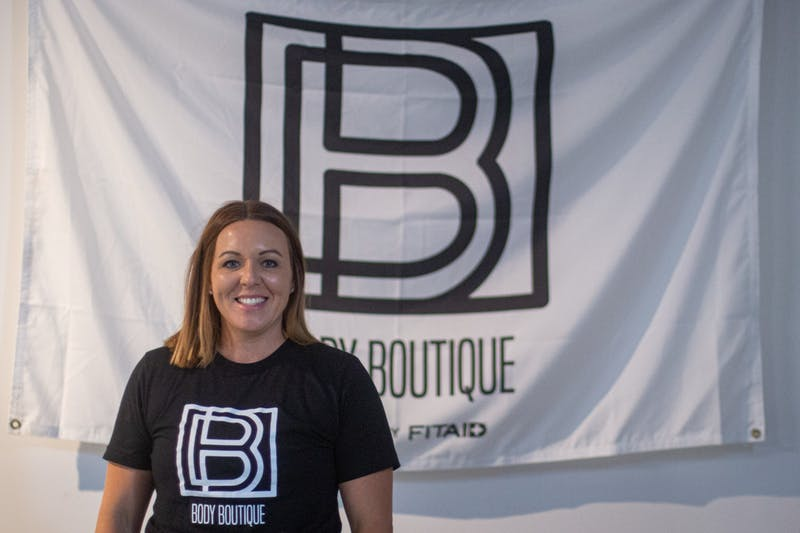 Brittney  Russell poses in front of a Body Boutique flag Sept. 10, 2020, at Body Boutique. Russell started Body Boutique out of a love for helping women reach their fitness goals. Demi Lawrence, DN