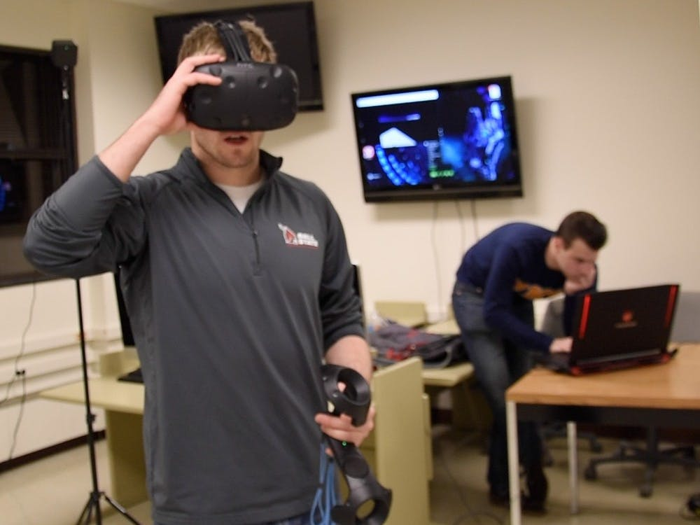 Bradley Ridge, a senior computer science major, adjusts his virtual reality headset before calibrating the controllers. Ridge is working with the computer science program in hopes of doing research with virtual reality and it's role in education. Patrick Calvert // DN