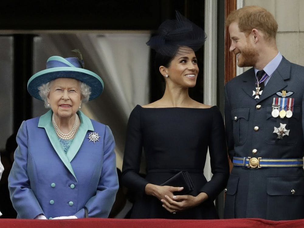 "In this July 10, 2018, file photo Britain's Queen Elizabeth II, Meghan, Duchess of Sussex, and Prince Harry watch a flypast of Royal Air Force aircraft pass over Buckingham Palace in London. As part of a surprise announcement distancing themselves from the British royal family, Harry and his wife Meghan declared they will ""work to become financially independent."" (AP Photo/Matt Dunham, File)"