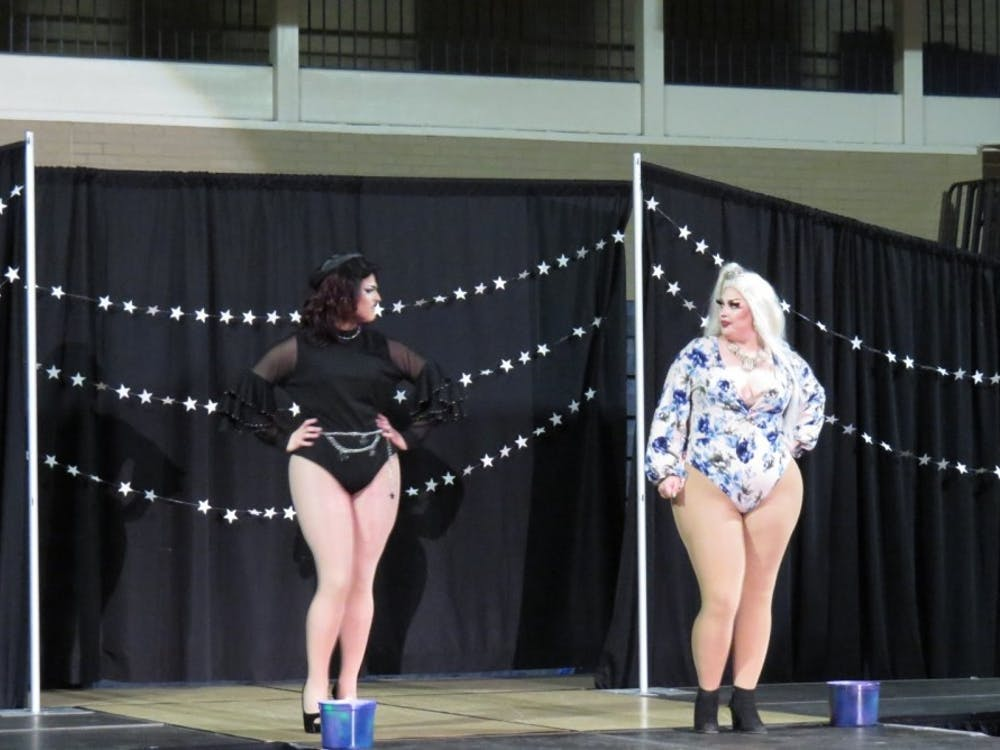 Two performers interact on stage during Spectrum's Gaylactic Drag Show April 6, 2019, at Ball Gym. Money raised at the drag show will benefit the National Center of Transgender Equality. Chase Martin, DN