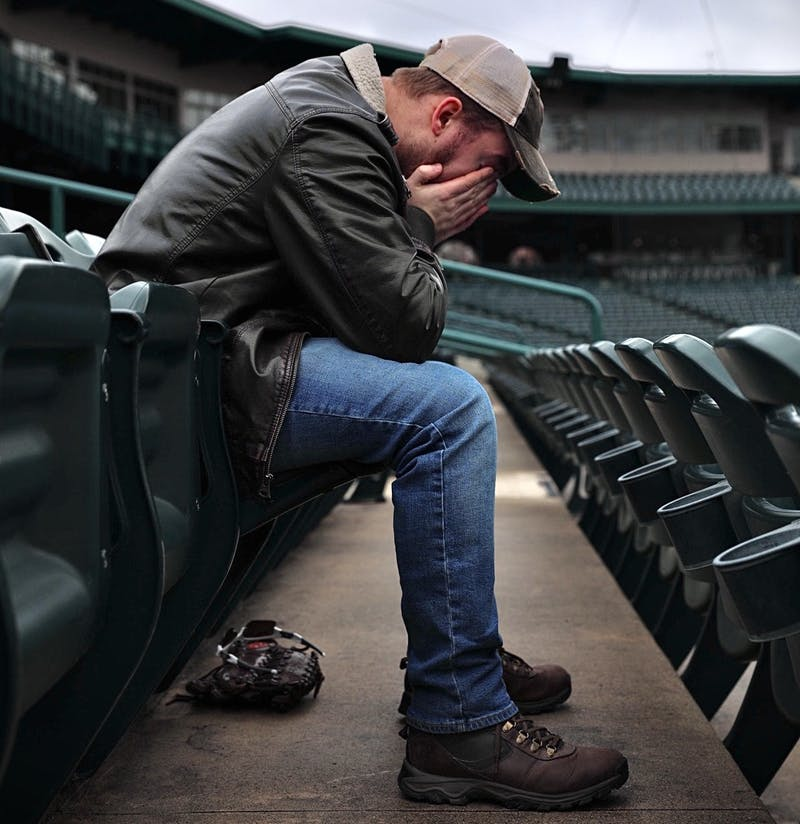 "Zach Piatt sits with his head in his hands March 22, 2020, at Parkview Field in Fort Wayne, Indiana. ""Anytime I walk into an empty sports venue, something feels off,"" Piatt said. ""It's not right. It's supposed to be buzzing."" Jacob Musselman, DN Illustration"