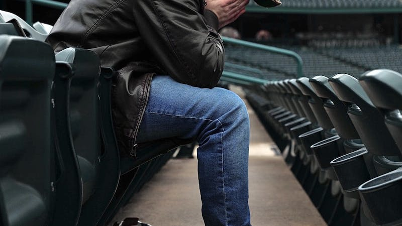 """Zach Piatt sits with his head in his hands March 22, 2020, at Parkview Field in Fort Wayne, Indiana. """"Anytime I walk into an empty sports venue, something feels off,"""" Piatt said. """"It's not right. It's supposed to be buzzing."""" Jacob Musselman, DN Illustration"""