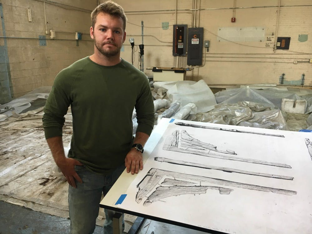 Senior Anthropology and History Major Evan Olinger stands next to a 3D rendering of a colonial-era ship's timbers at the Washington Navy Yard during his internship over the summer. Photo Provided