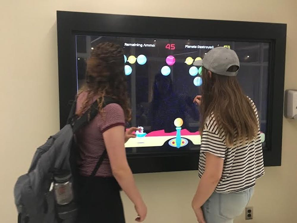 """<p>Freshman telecommunications major Sam Essex and sophomore telecommunications and design technology major Selena Webb play """"Charlie Destroys Worlds"""" outside of the Digital Corps office. The game was developed this semester by senior animation major Marisa Lozano. Michelle Kaufman // DN</p>"""