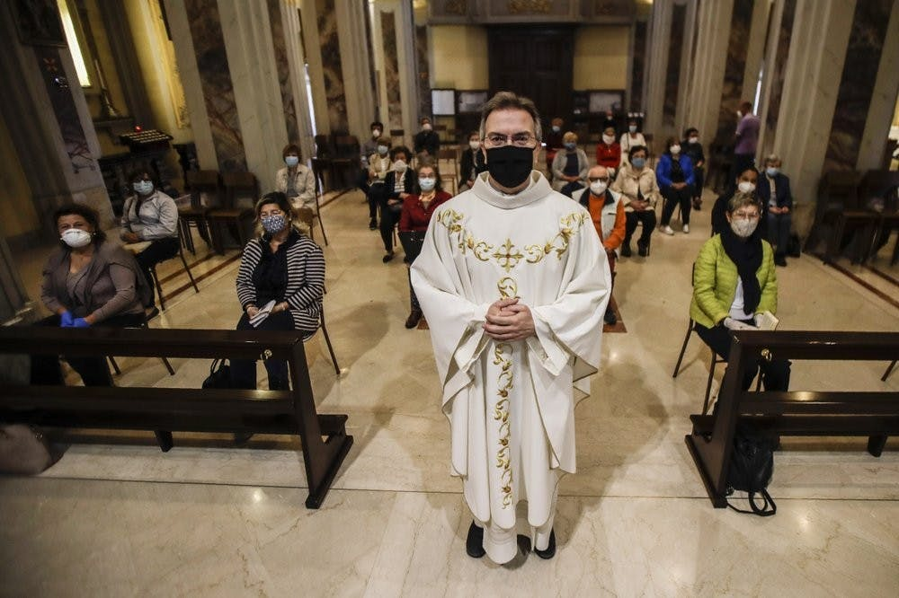 Parson Don Giuseppe Corbari poses prior to the start of a mass with faithfuls the SS. Quirico and Giulitta Church May 18, 2020, in Robbiano di Giussano, northern Italy. Masses with the presence of faithful resumed Monday, as Italy is easing its lockdown measures. (AP Photo/Luca Bruno)